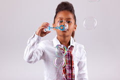 Little African Asian girl blowing soap bubbles Stock Images
