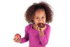 Little African Asian girl eating a chocolate cake. And holding an apple, isolated on white background Stock Image