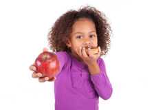 Little African Asian girl eating a chocolate cake. And holding an apple, isolated on white background Royalty Free Stock Photo