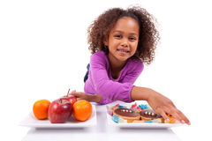 Little African Asian girl hesitating between fruits or  candy Royalty Free Stock Photo