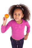 Little African Asian girl holding a tangerine Royalty Free Stock Photo
