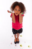 Little African Asian girl with painted hands. In colorful paints stock photos