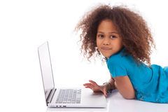 Little african asian girl using a laptop. On white background royalty free stock image
