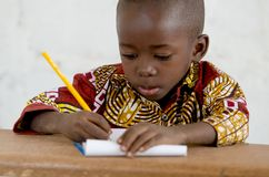 Little African Black Baby Boy in the Classroom Writing Notes. Candid shot of black African children. By buying this image you support our charity projects in Stock Images
