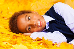 Little African boy lays on autumn yellow leaves Royalty Free Stock Image