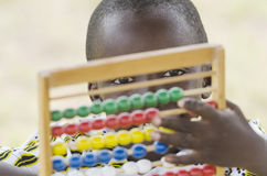 Little African boy learning to count with abacus. Portrait of african boy counting on abacus frame and looking at camera Royalty Free Stock Photo