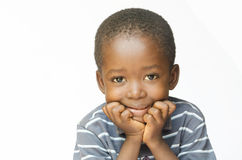 Little African child holding his head in his hands thinking about his future. Isolated on white. Little African boy making a facial expression. Here he is Stock Photo