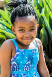 Little african girl in blue dress outdoors. Close up portrait of cute african girl in blue dress and braided hairstyle outdoors Royalty Free Stock Images