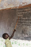 Little African girl in classroom working on exercises. Girl pointing on chalkboard in classroom Royalty Free Stock Photography