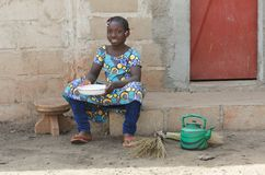 Little African Girl Cooking Rice Outdoors Smiling at Camera. Candid Shot of African Children in an African City. By buying this image you support our charity Royalty Free Stock Images