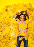 Little African girl covered with autumn leaves Royalty Free Stock Photos