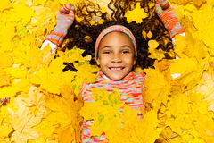 Little African girl covered with maple leaves Stock Images