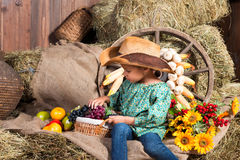 Little african girl in cowboy hat sitting on straw bag with fruits Royalty Free Stock Images