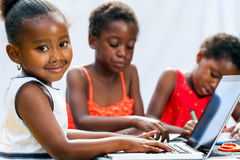 Little African girl doing homework on computer with friends. royalty free stock photography