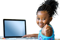 Little african girl doing thumbs up at desk. Royalty Free Stock Photography