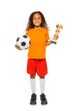 Little African girl holding soccer ball and prize. Happy African black girl with curly hair holding soccer ball and winners prize cup wearing sport team uniform royalty free stock photos