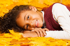 Little African girl lays on autumn yellow leaves Royalty Free Stock Photos