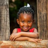 Little african girl leaning on wooden fence. Close up portrait of pretty african youngster leaning on wooden fence outdoors stock photos