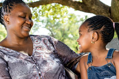 Little african girl looking at mom in park. Royalty Free Stock Images
