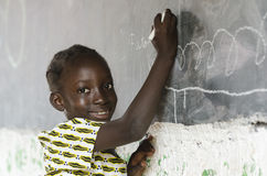 Little African girl studying in front of blackboard. Girl standing and writing on chalkboard in classroom Stock Photography
