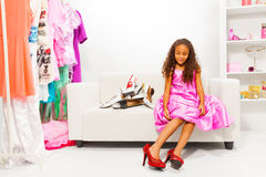Little African girl trying on mothers shoes Stock Images