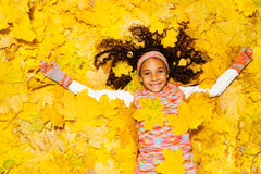 Little African girl under yellow maple leaves Stock Photos
