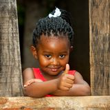 Little african girl at wooden fence with thumbs up. Portrait of small african girl doing thumbs up at wooden fence royalty free stock image