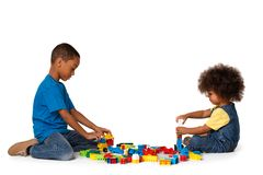 Little african kids playing with lots of colorful plastic blocks. Isolated. Two little cute african american children playing on the floor with lots of colorful royalty free stock photo