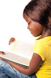 Profile of a little african school girl. Profile of a cute african school child girl reading book, education concept stock photos