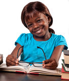 Smiling schoolgirl studying. Portrait of a smiling black schoolgirl sat at a table studying with an open book and glasses Stock Image