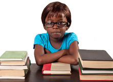Little African school girl by stack of books. Cute African school girl wearing glasses looking bored over white background royalty free stock image