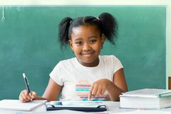 Little african student sitting at desk with blank black board in. Close up portrait of cute little african student writing and working at desk with digital Stock Images