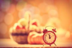 Little alarm clock and pumpkin Stock Images