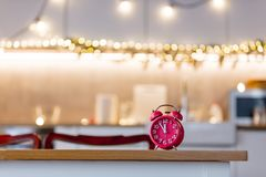 Little alarm clock on a table with Christmas lights. On background. Kitchen interior stock photo