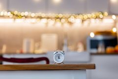 Little alarm clock on a table with Christmas lights. On background. Kitchen interior royalty free stock photos