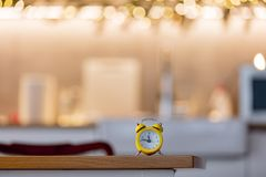 Little alarm clock on a table with Christmas lights. On background. Kitchen interior royalty free stock images