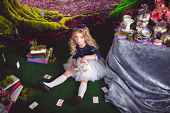 Little Alice in Wonderland pouring tea. Little sitting on the floor girl in a beautiful dress in the image of Alice in Wonderland pouring tea Royalty Free Stock Photos