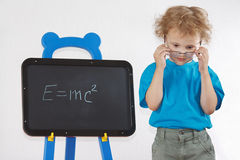 Little amazed boy with glasses shows formula Stock Photography