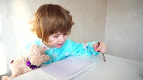 Little american girl with pink pen learns to draw.n stock video