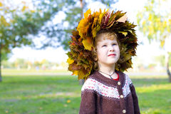 Little amusing girl in a wreath from autumn leaves Royalty Free Stock Photos