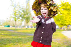 Little amusing girl in a wreath from autumn leaves Royalty Free Stock Image