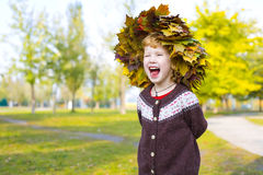Little amusing girl in a wreath from autumn leaves Royalty Free Stock Photo