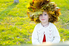 Little amusing girl in a wreath from autumn leaves Stock Photography