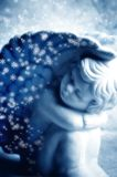 Little angel. With snow flakes in blue tonality Royalty Free Stock Images