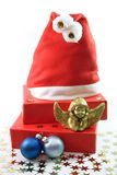 Little Angel. Santa Hat, red presents, golden angel figure, blue chrismas tree balls on light background stock photos