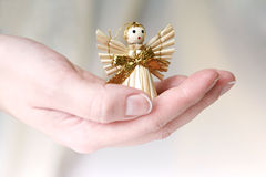 Little Angel. A hand giving little straw angel Royalty Free Stock Images