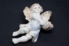 little angel with basket of fruits and blue tunic looking at the sky on black background. Closeup royalty free stock images