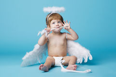 Little angel on blue background Stock Photos