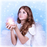 Little angel. Closeup portrait of cute little angel looking up, holding candle in hands and praying to God, snow falling background, Christmas costume party Stock Image