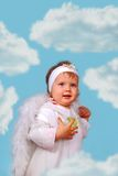 Little angel among the clouds. Little baby girl with white wings as angel among the clouds Stock Photo